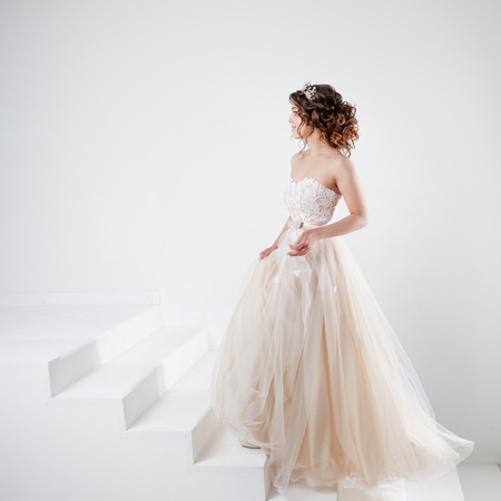 Concept of bride going towards future happiness. Portrait of a beautiful girl in a wedding dress. Stock Photo