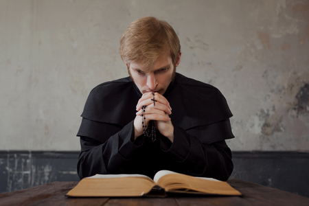 Priest read the Bible. Handsome young catholic priest praying to God