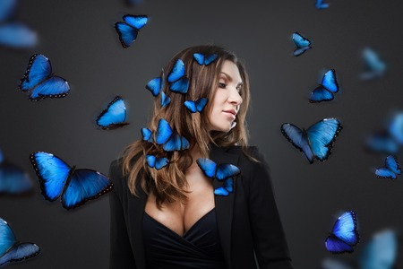 Beauty Fashion Model Girl surrounded by swarms of butterflies. Grey background Stock Photo