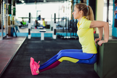 Girl in fitness club. young sportswoman doing squats using bench in gym Stock Photo