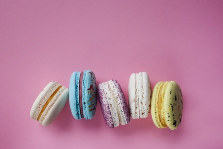 French colorful macarons on a pink background