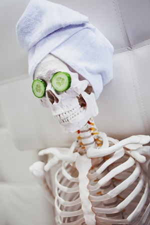 Skeleton in Spa salon with towel on her head and mask on her face, relaxes, care themselves. An absurd concept, social parody. Take care of beauty and forget about inner peace Stock Photo