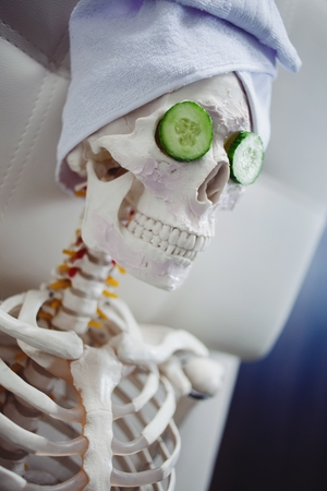 deceptive: Skeleton in Spa salon with towel on her head and mask on her face, relaxes. An absurd concept, social parody. Take care of beauty and forget about inner peace