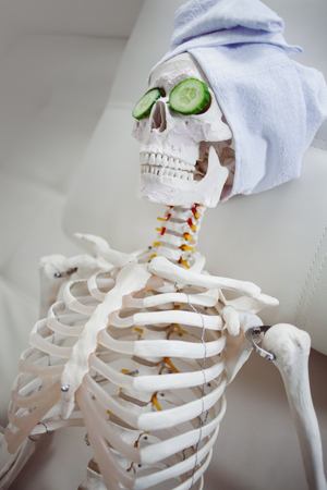 Skeleton in Spa salon with towel on her head and mask on her face, relaxes. An absurd concept, social parody. Take care of beauty and forget about inner peace