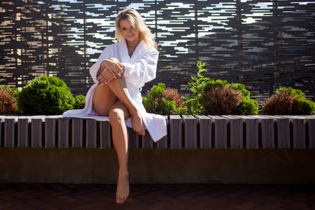 autocuidado: Young smiling woman in Bathrobe on the terrace of a luxury hotel