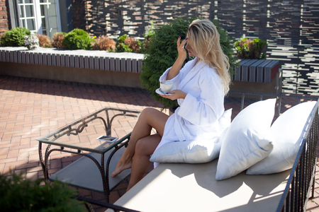 autocuidado: Beautiful young woman in Bathrobe sitting on terrace and drink coffee
