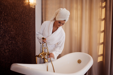 Young woman in Bathrobe, turns water on in the tub