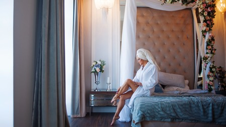 bathroom interior: To use the cream for the body. Young woman in a Bathrobe, interior of the hotel