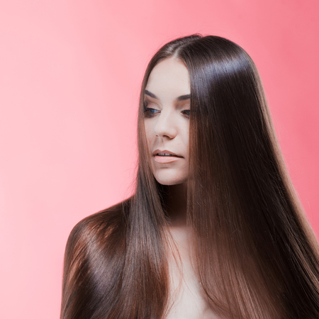 Beauty portrait of brunette with perfect hair, on a pink background. Hair care Zdjęcie Seryjne