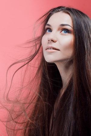 gloss: Beauty portrait of brunette with perfect hair, on a pink background. Hair care Stock Photo