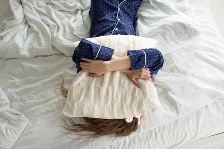 Te lui om uit bed te komen, bedekt een vrouw haar gezicht met een kussen Stockfoto