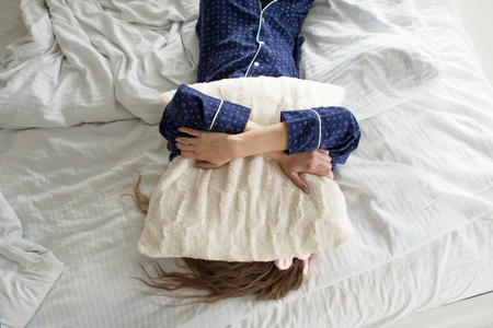 Too lazy to get out of bed, woman covers her face with a pillow