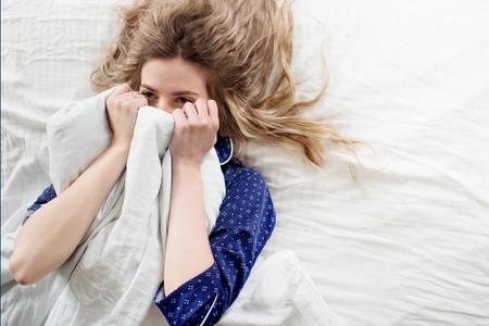 Cute blonde in her bed in blue pajamas, under a blanket Stockfoto