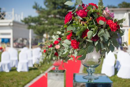 Decoración de boda Registro de bodas al aire libre. Ramos de lujo con flores rojas Foto de archivo - 85607251