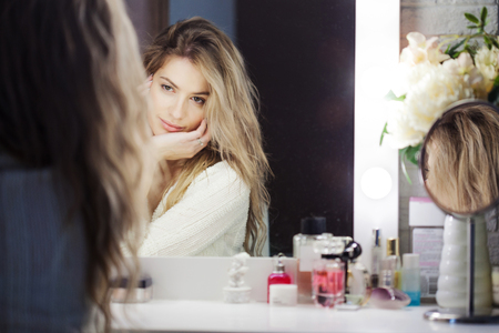 woman mirror: Amazing young woman doing her makeup in front of mirror. Portrait of beautiful girl near cosmetic table Stock Photo