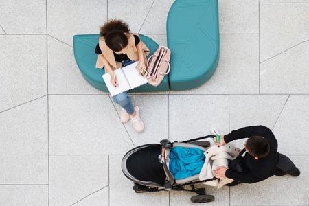 Business lady plannen in haar dagboek, in de buurt van wandelen familie man met wandelwagen. Uitzicht vanaf de top, concept Stockfoto