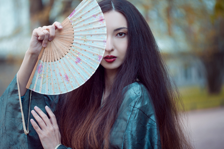 Portrait of young beautiful Asians in grey kimono and with a fan Stok Fotoğraf