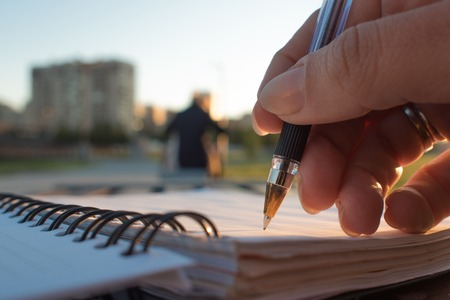 Close-up, writing in a notebook, develop a plan of action