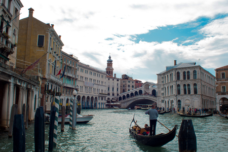 VENICE, ITALY - OCTOBER 8 , 2017: Gondolier floats on the Grand Canal, the Rialto bridge in the background Editorial