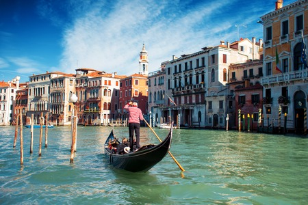 Gondolier floats on the Grand Canal, the Rialto bridge in the background Stock Photo