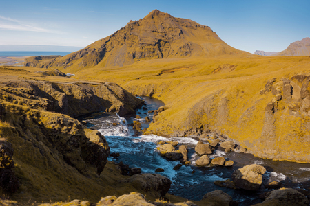 Iceland, mountain river, rock in the background Stock Photo