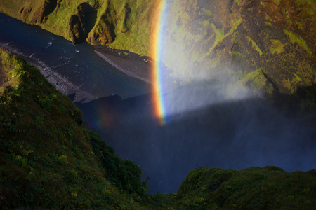 Rainbow on the background of rocks, foot of Skogafoss waterfall, Iceland