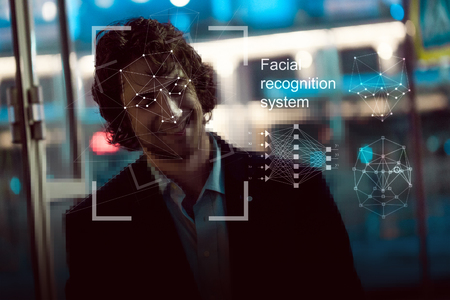 Facial recognition system, concept. Young man on the street face recognition Foto de archivo