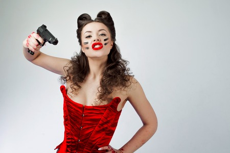 Charming lady in red corset. Sweetie Belle in war paint, girl power Stockfoto