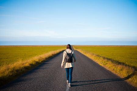 Woman tourist with backpack on the background road. Toward the goal Stockfoto