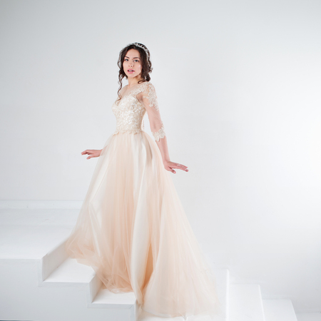 Portrait of a beautiful girl in a wedding dress. Bride in a luxurious dress standing on the stairs, climb up