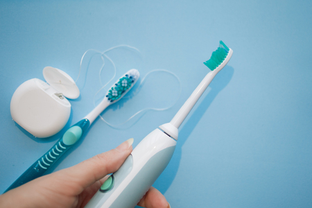 Choose a modern toothbrush. The hand holding the sonic toothbrush