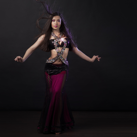 Beautiful girl in crimson dress dancing Oriental dance