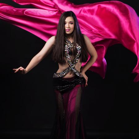 Beautiful girl in crimson dress dancing Oriental dance