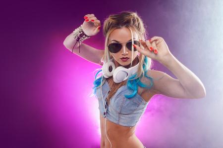 Muchacha de moda joven en estilo del disco. Escuchando música y disfrutando. Estilo retro Foto de archivo - 92557692