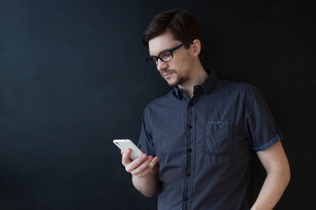 Young adult guy in a grey shirt uses a smartphone. Business portrait on textured black background Foto de archivo