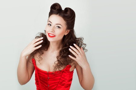 Charming lady in a red corset, pin-up hairstyle