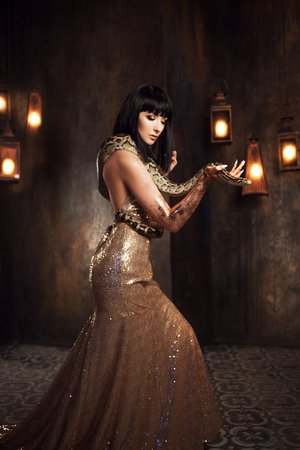 Beautiful and mysterious brunette in a gold dress and with a snake