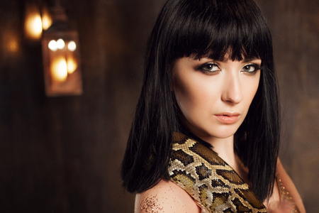 Beautiful brunette in a gold dress and with a snake. Close-up