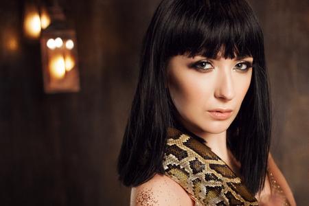 Mooie brunette in een gouden jurk en met een slang. Detailopname