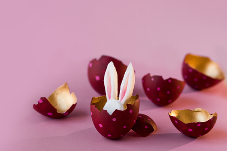 Easter concept. Colored eggs on a pink background, Easter Bunny hiding inside Stock Photo