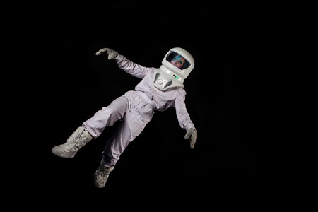 Astronaut in space, in zero gravity on black background. Man in space, falling