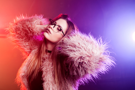 Fashionable young woman in a fluffy pink coat, neon light. Portrait of beautiful trendy girl