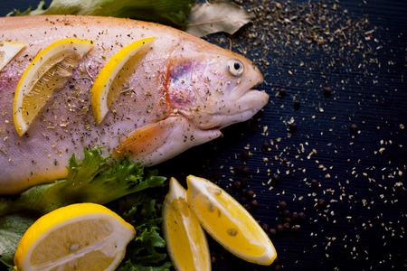 Fresh trout and ingredients to prepare fish dishes on a black table Imagens