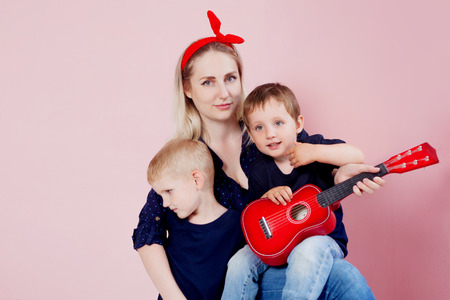 Happy young woman with sons . Portrait on a pink background. Cheerful family Stock Photo