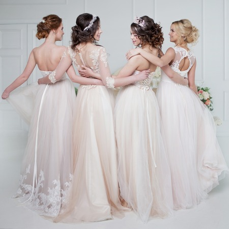 Bride in wedding salon. Four beautiful girl are in each others arms. Close-up lace skirts