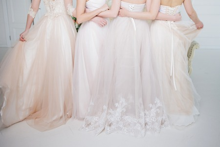 Bride in wedding salon. Four beautiful girl are in each other's arms. Close-up lace skirts 免版税图像