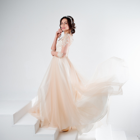 Portrait of a beautiful girl in a wedding dress. Bride in a luxurious dress on a white background