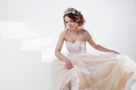 Portrait of a beautiful girl in a wedding dress. Dancing Bride, white background.