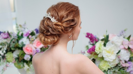 Back view of amazing young bride. Red head woman seat on the chair. Elegant hairstyle. Hair style with curls.
