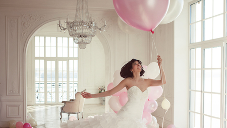 Young woman in wedding dress in luxury interior flies on pink and white balloons. Charming young bride brunette with short haircut in stylish Quinceanera dresses.